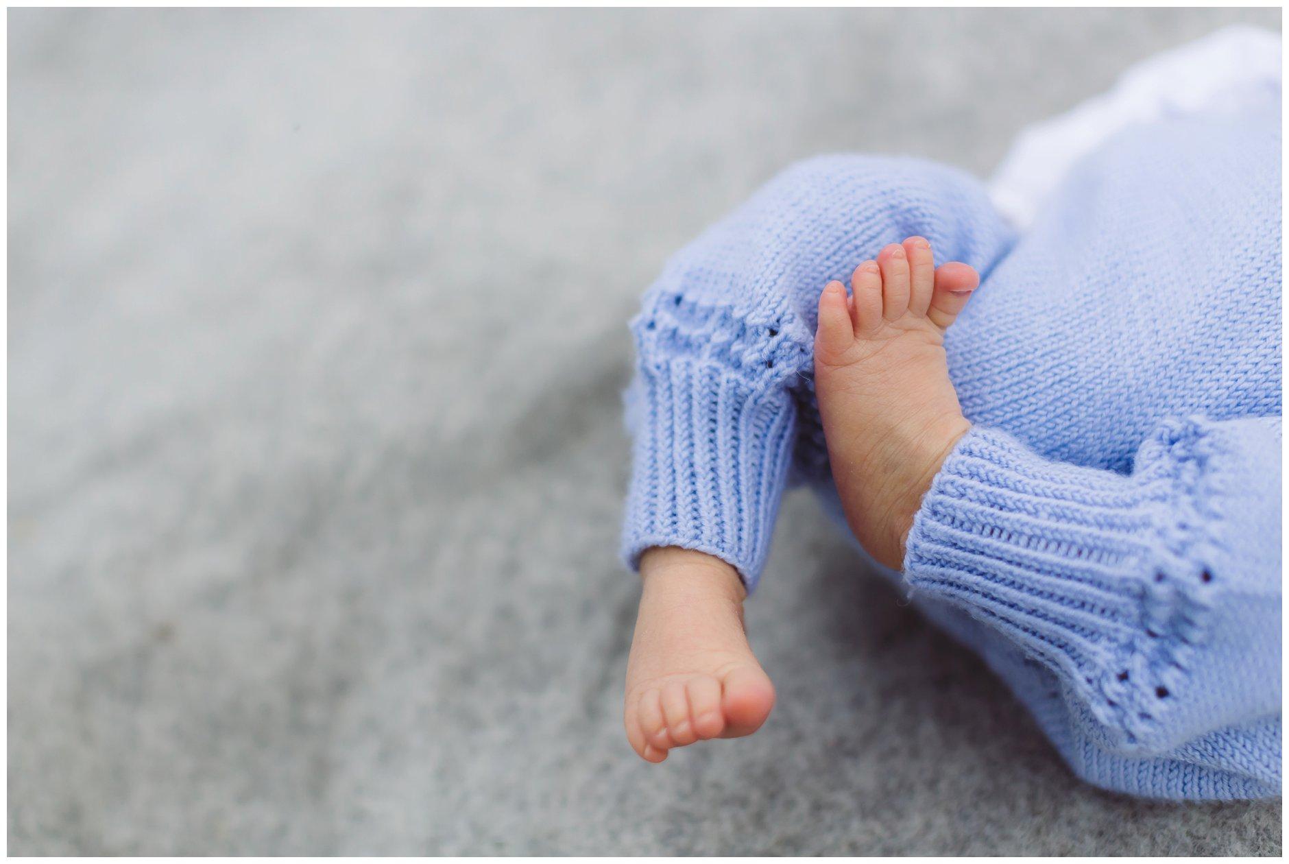 Utendørs nyfødtfotografering babyføtter